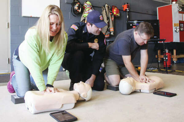 Stephanie Church Hein and Austin Hein practice compressions on CPR dummies with the help of Godfrey Fire Chief Erik Kambarian during the departments open house Saturday. The event was held at Station 2 and featured a number of exhibits. A major emphasis was on CPR, in part because of Sudden Cardiac Arrest Awareness Month.