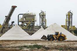 A WildHorse Resource Development front end loader drives past piles of sand for use in fracking operations at the new sand mine Tuesday Oct. 2, 2018 in Caldwell.