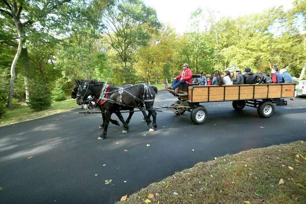 Children and their parents begin a horse drawn wagon ride during the Autumn Festival at the Ansonia Nature Center on October 20, 2018.