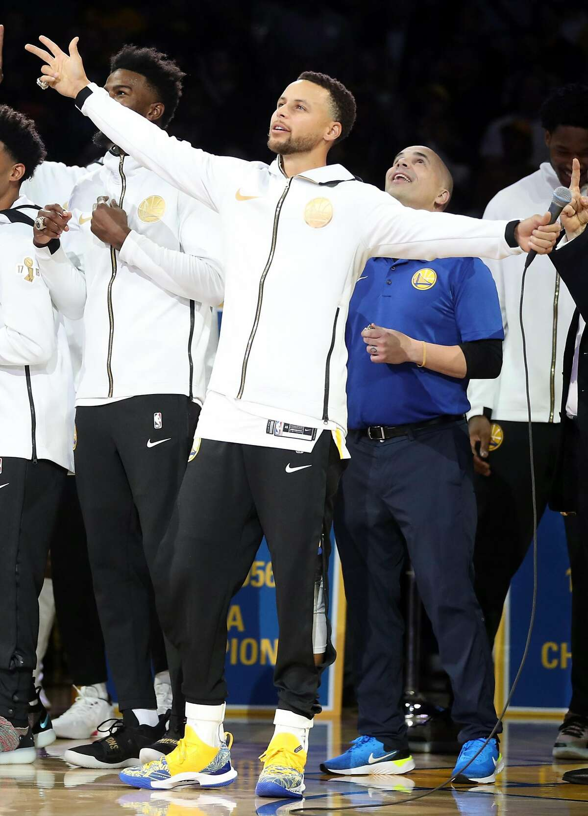 Golden State Warriors' Stephen Curry and equipment manager Eric Housen watch as 2018 NBA Championship banner is unveiled during ceremony before Opening Night game against Oklahoma City Thunder at Oracle Arena in Oakland, Calif. on Tuesday, October 16, 2018.