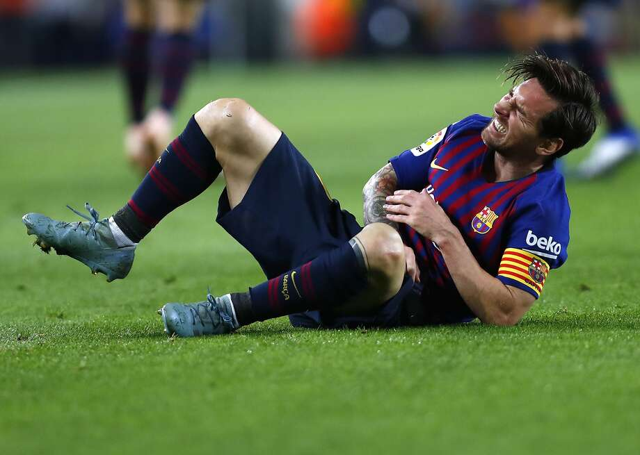 Barcelona's Lionel Messi writhes in pain after scoring against Sevilla at Camp Nou. Photo: Manu Fernandez / Associated Press