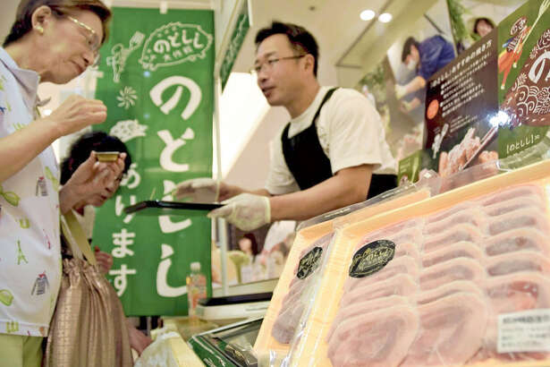 A Hakui, Japan, city official promotes notoshishi meat at a department store in Kanazawa on Sept. 5.