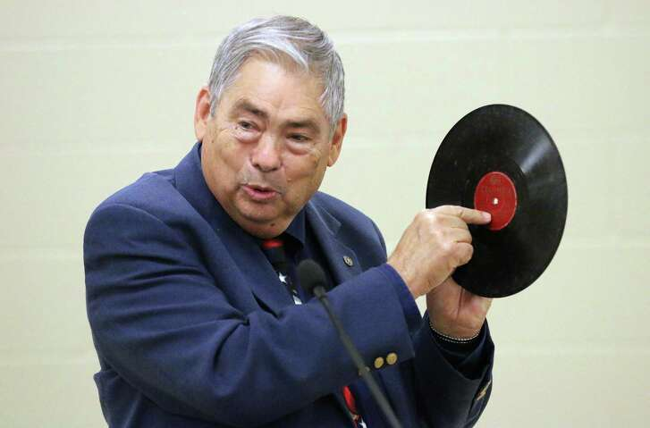 Texas State Historian Bill O'Neal holds up a 78 album. He was describing the vinyl for some of those who had never seen the object used to record early music, especially country music in Texas.