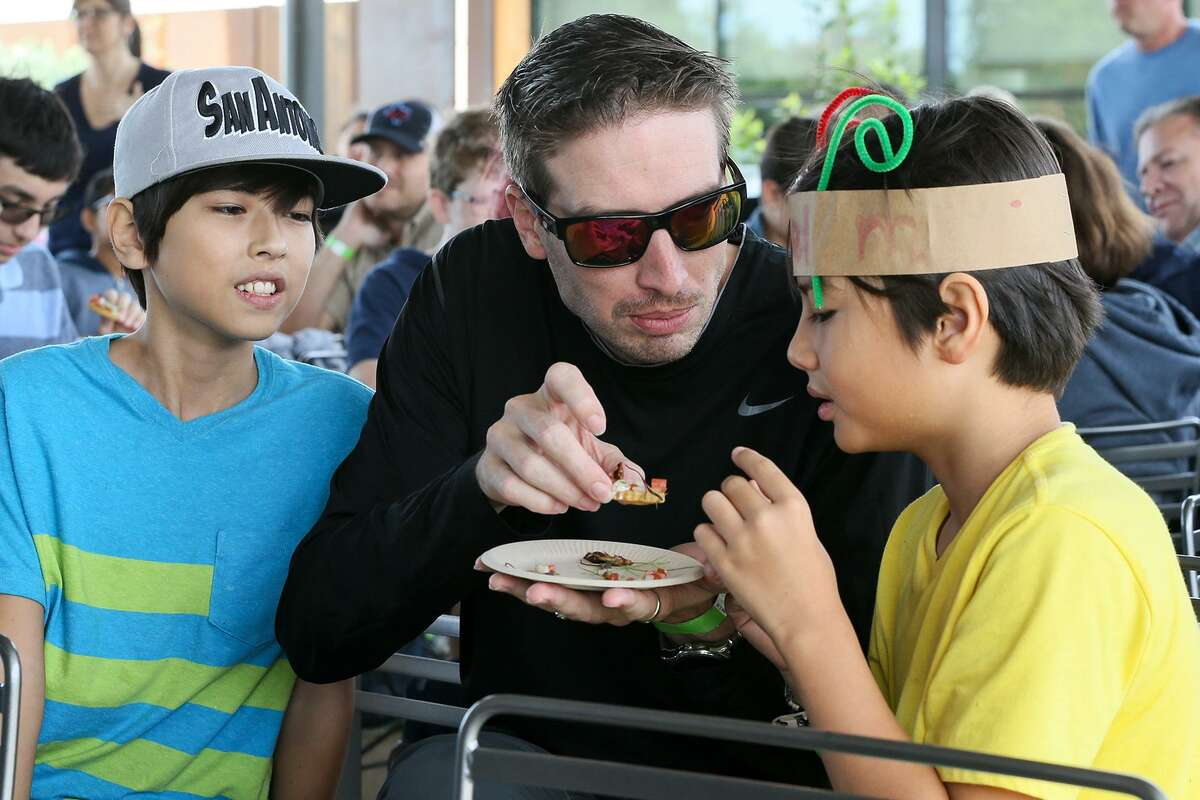 """Edmond Madson (left), 11, watches with apprehension as his father, Samuel Madson, offers a Chapulines Taco (grasshopper taco) to his brother, Gabriel Madson, 9, at the """"Incredible, Edible Insects"""" lunch at the Botanical Garden on Saturday, Oct. 20, 2018. The lunch, where local chefs served recipes made with insects, was part of the Monarch Butterfly and Pollinator Festival."""