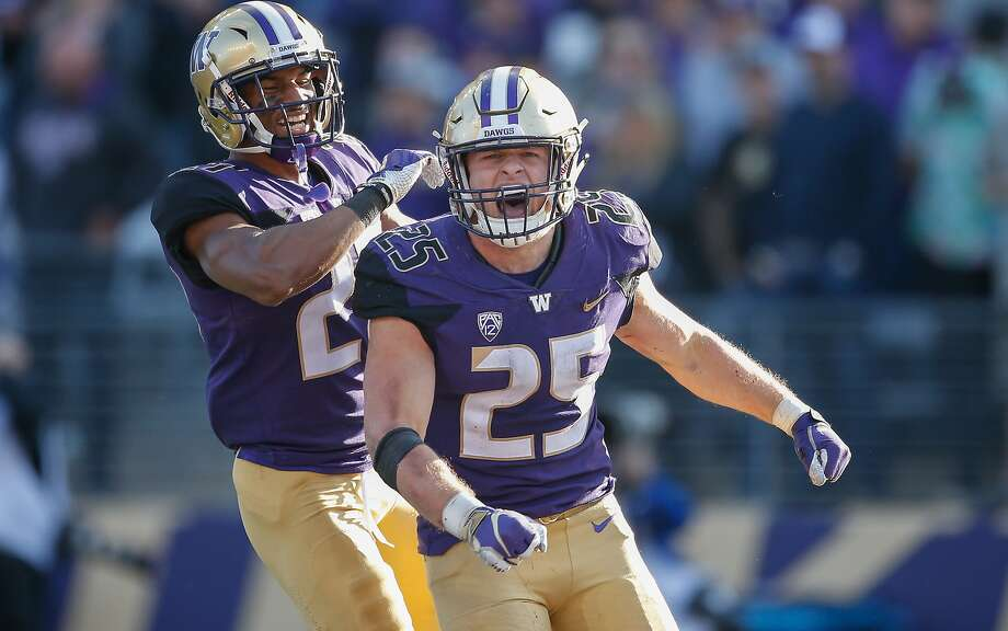 Washington linebacker Ben Burr-Kirven (25) is congratulated by defensive back Keith Taylor after making an interception in the fourth quarter against Colorado. Photo: Otto Greule Jr / Getty Images