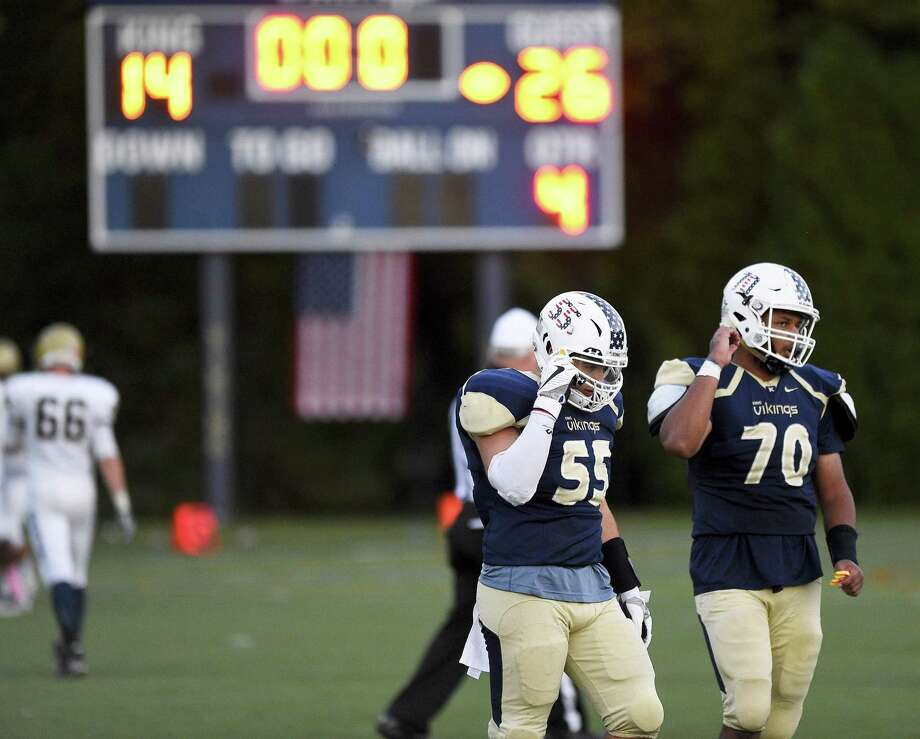 King's Alex Canevari (55) and Lewis Baer (70) walk off the field following the Vikings' 26-14 loss against Rye Country Day School in a varsity football game played on Saturday in Stamford. Photo: Matthew Brown / Hearst Connecticut Media / Stamford Advocate
