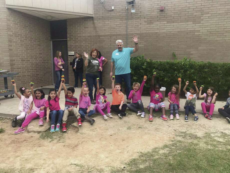 Conroe Noon Lions Club members Donna Trice-Drummond, left, and Rick Camp, right, cheer on first graders at Reaves Elementary School during their Bee Club incentive party for excellent grades and conduct.