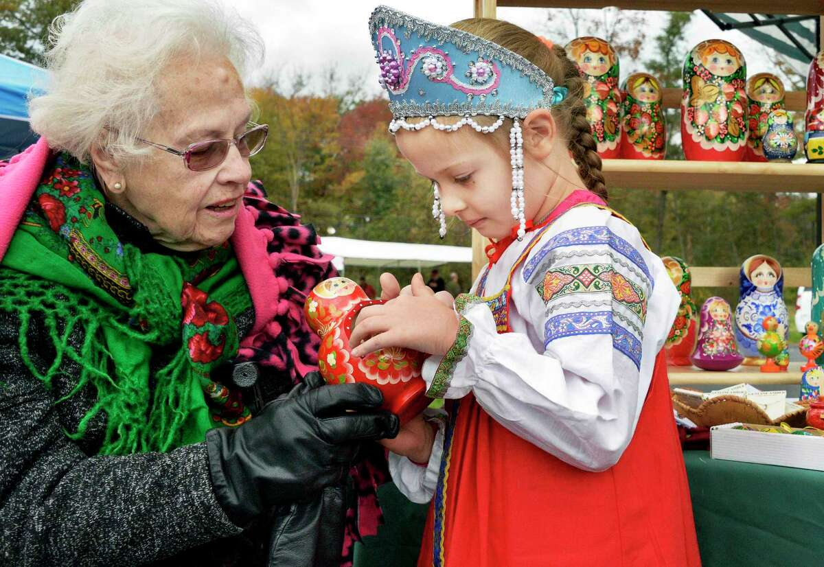 Margo Beighey of Clifton Park shows 6-year-old Maria Timofeer of Guilderland a traditional Russian doll during the Taste of Russia Festival at the Nativity of the Most Holy Mother church Saturday Oct. 20, 2018 in Colonie, NY. (John Carl D'Annibale/Times Union)