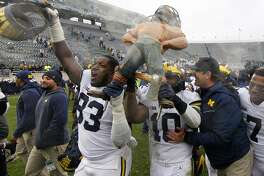Michigan coach Jim Harbaugh, right, congratulates Devin Bush (10) as Bush and Lawrence Marshall, left, carry the Paul Bunyan trophy following a 21-7 win over Michigan State in an NCAA college football game, Saturday, Oct. 20, 2018, in East Lansing, Mich. (AP Photo/Al Goldis)