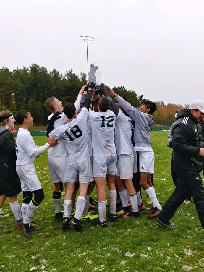 Dow High soccer players lift the district championship trophy on Saturday after beating Traverse City West 4-3 in the district final in Traverse City. (Photo provided)