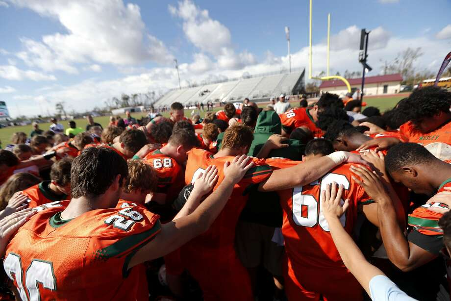 Coaches and players from Mosley High pray together after their loss to Pensacola High, in the aftermath of Hurricane Michael in Panama City, Fla., on Saturday. Photo: Gerald Herbert / Associated Press