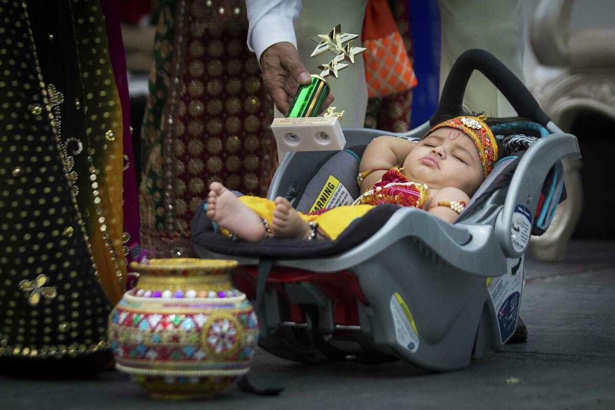 Rohan Soni, who is seven month old is presented with a third place best costume award while he sleeps, Saturday, Oct. 20, 2018, in Sugar Land. Soni was dressed as the Hindu god Bal Krishna during the a Diwali Festival of Lights event. The actual holiday will be November 7.