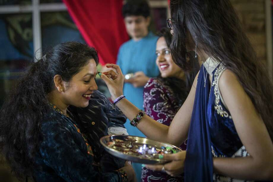 Tikka is applied on the forehead of Sushma Panthi, left, as she is welcomed by Kinal Mittal, 17, to the Diwali Festival of Lights event in Sugar Land, Saturday, Oct. 20, 2018. Photo: Marie D. De Jesús, Houston Chronicle / Staff Photographer / © 2018 Houston Chronicle