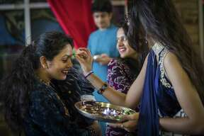 Tikka is applied on the forehead of Sushma Panthi, left, as she is welcomed by Kinal Mittal, 17, to the Diwali Festival of Lights event in Sugar Land, Saturday, Oct. 20, 2018.