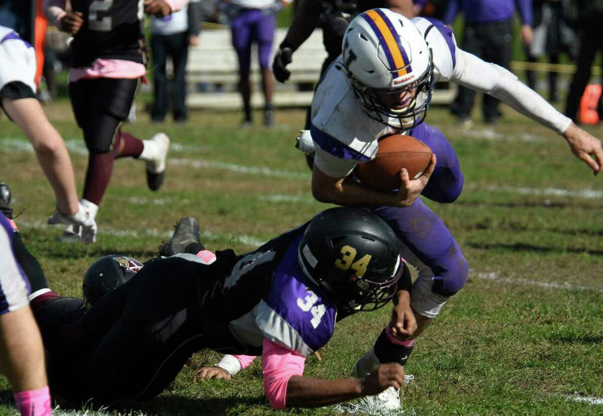 Voorheesville quarterback Ian Owens stumbles after a tackle to the legs from from Holy Trinity center Nelon Priest during a game on Saturday, Oct. 20, 2018 in Schenectady, N.Y. (Jenn March, Special to the Times Union )