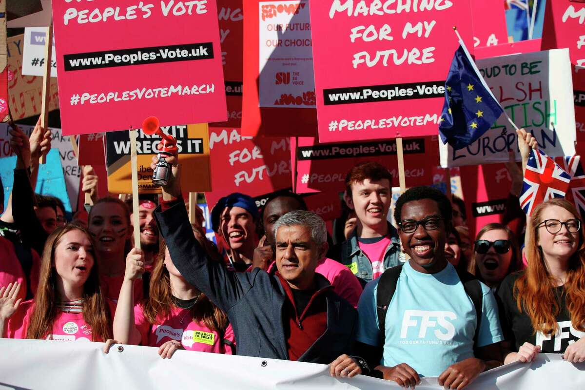 Mayor of London Sadiq Khan, front centre, holds a klaxon horn, as he joins protesters in the People's Vote March for the Future, in London, Saturday Oct. 20, 2018. Some thousands of protesters are marching through central London, Saturday, to demand a new referendum on Britain?'s Brexit departure from the European Union. (Yui Mok/PA via AP)