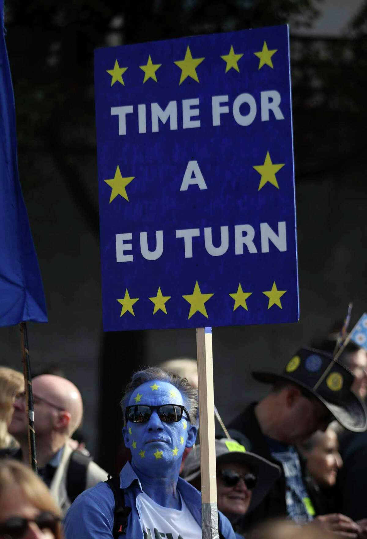 An anti-Brexit campaigner with his face painted in the colours of the European Union flag, during the People's Vote March, in London, Saturday Oct. 20, 2018. Some thousands of protesters are marching through central London, Saturday, to demand a new referendum on Britain?'s Brexit departure from the European Union. (Yui Mok/PA via AP)