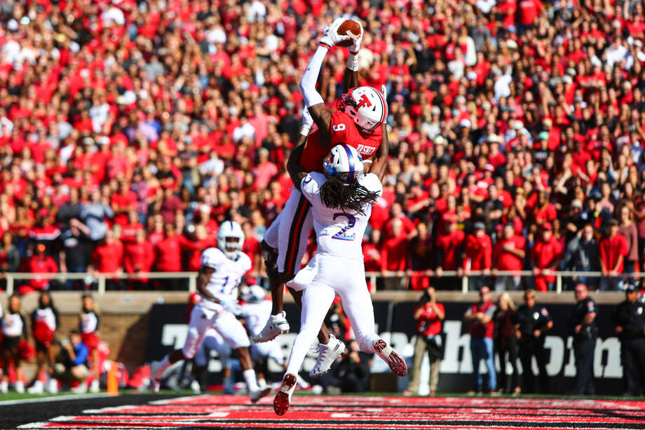 WELCOME BACK In his first game back, Texas Tech wide receiver T.J. Vasher catches a touchdown pass from Alan Bowman (not pictured) over Kansas cornerback Corione Harris during the Red Raiders' 48-16 Homecoming win over the Jayhawks on Saturday at Jones AT&T Stadium in Lubbock. Photo: Brad Tollefson/Lubbock Avalanche-Journal