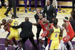Houston Rockets' Chris Paul, far left, is held back by Los Angeles Lakers' LeBron James, second from left, after Paul fought with Lakers' Rajon Rondo, far right, during the second half of an NBA basketball game Saturday, Oct. 20, 2018, in Los Angeles. The Rockets won, 124-115. (AP Photo/Marcio Jose Sanchez)