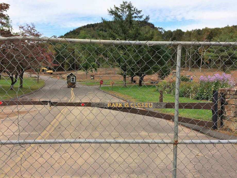 A fence blocks the main entrance to Sleeping Giant State Park in Hamden, which was damaged by a tornado in May. State officials do not have an estimate for when the park will reopen, and it will definitely remain closed for the fall foliage season. Photo: Michelle Tuccitto Sullo