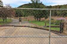 A fence blocks the main entrance to Sleeping Giant State Park in Hamden, which was damaged by a tornado in May. State officials do not have an estimate for when the park will reopen, and it will definitely remain closed for the fall foliage season.