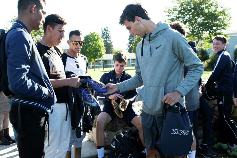 Santiago Silvani, an Old Greenwich resident and a captain of King School's varsity soccer team, hands cleats to Santiago, a 19-year-old visiting from Colombia. He and four other young men came to Stamford on behalf of their orphanage and the Orphaned Starfish Foundation, an international nonprofit that promotes computer literacy so orphans can be gainfully employed. Photo: Kathleen O'Rourke / Contributed / Greenwich Time
