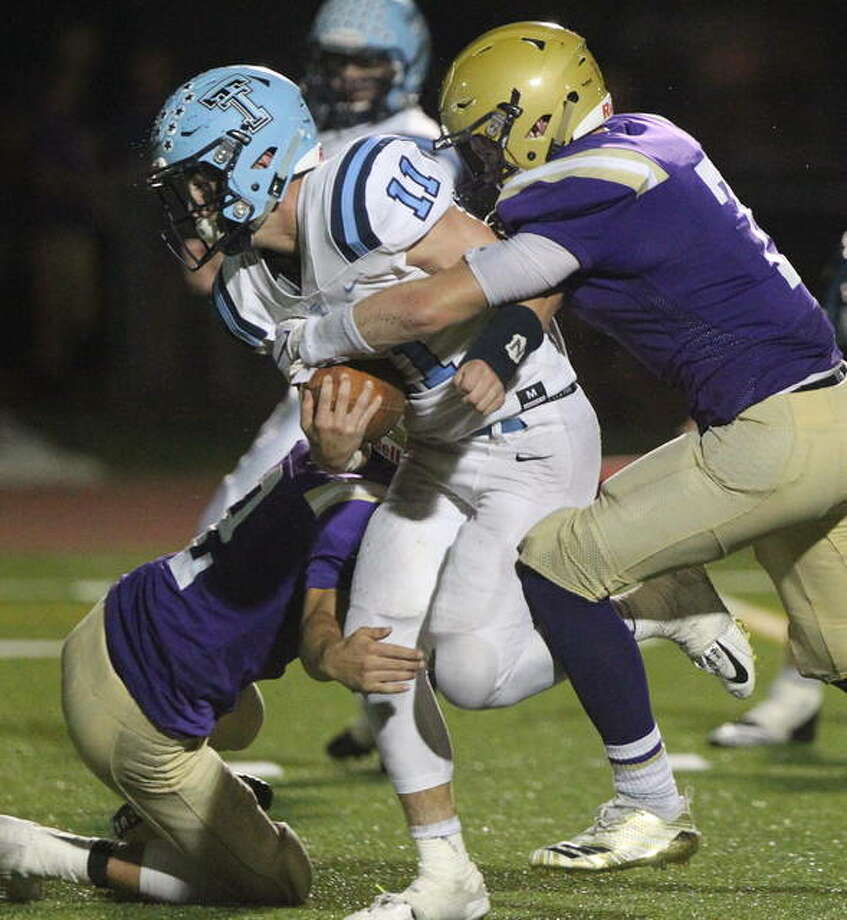 Triopia's Zach Thompson struggles forward during a game against Routt in Jacksonville earlier this season. Both teams are headed to the playoffs. Photo: Dennis Mathes | Journal-Courier