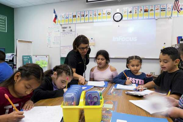Second-grade teacher Peggy Trejo work with students at Collier Elementary on Oct. 12, 2018. Collier is in the Harlandale Independent School District.