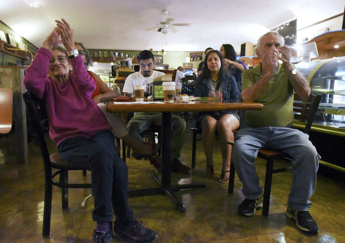 Marilyn Keene, left, her husband, Tom, right, and others applaud during open mic night at Barrio Barista, where poets from all walks of life connect with the audience