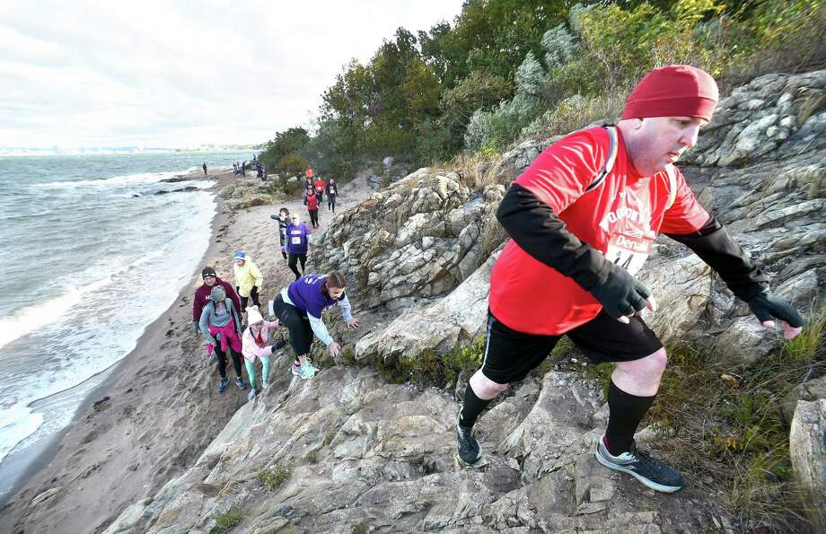 Competitors run up a section of rocky shore, one of 15 man-made and natural obstacles, during the first heat of Denali's 7th Annual Fall Run the Gauntlet Race at Lighthouse Point Park in New Haven Sunday. Photo: Arnold Gold / Hearst Connecticut Media / New Haven Register
