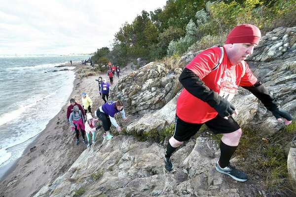 Competitors run up a section of rocky shore, one of 15 man-made and natural obstacles, during the first heat of Denali's 7th Annual Fall Run the Gauntlet Race at Lighthouse Point Park in New Haven Sunday.