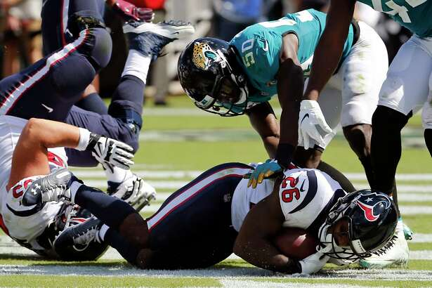 Houston Texans' Lamar Miller (26) dives in the end zone to score a touchdown on a 5-yard run in front of Jacksonville Jaguars linebacker Telvin Smith (50) during the first half of an NFL football game, Sunday, Oct. 21, 2018, in Jacksonville, Fla. (AP Photo/Stephen B. Morton)