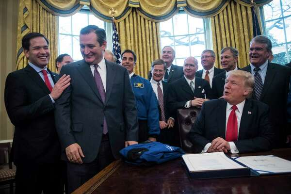 President Donald Trump jokes with Sen. Marco Rubio, R-Fla., and Sen. Ted Cruz, R-Texas, after signing a bill to increase NASA's budget to $19.5 billion in the Oval Office of the White House in on March. 21, 2017.