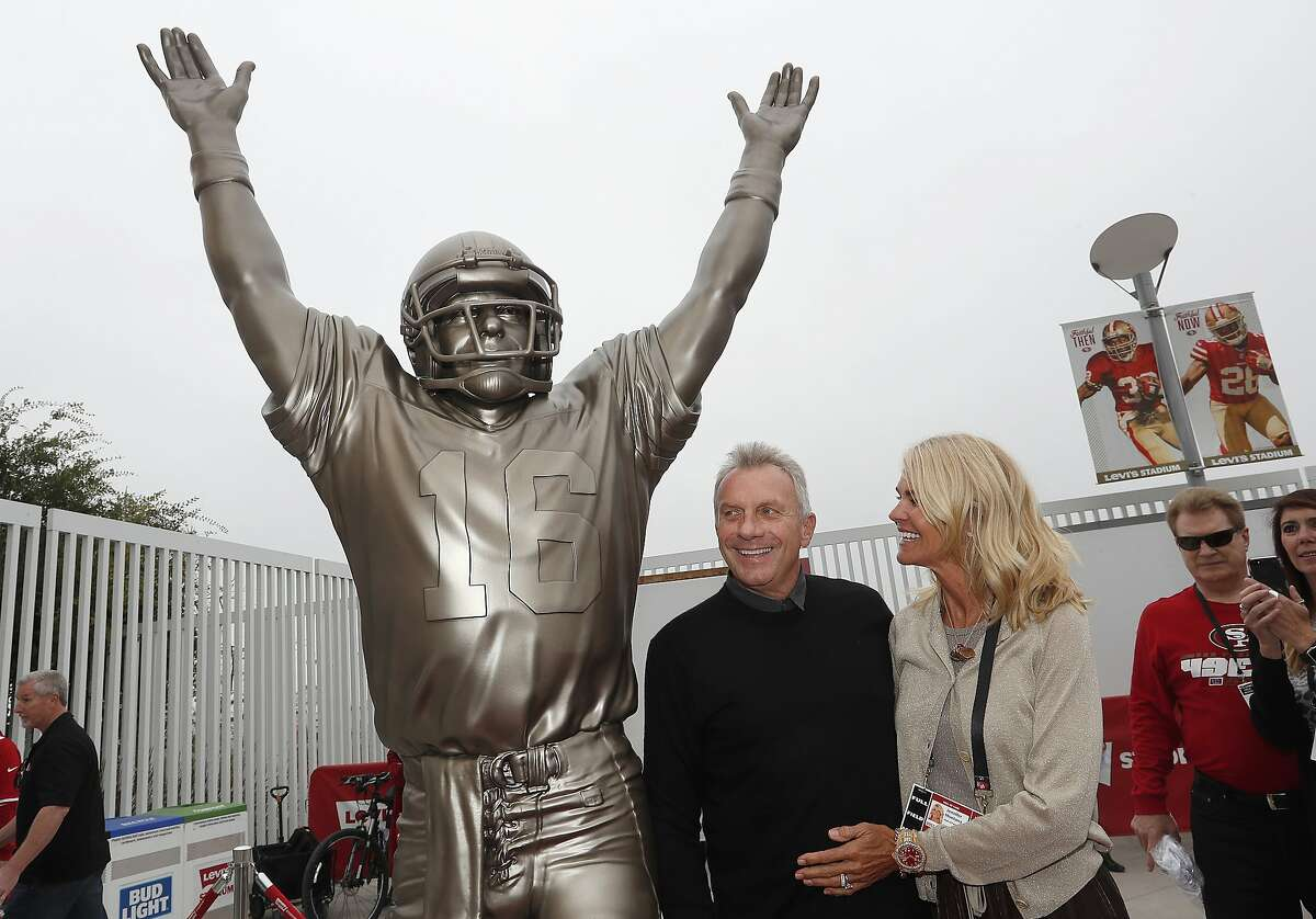 """FILE - Former San Francisco 49ers quarterback Joe Montana, center, and his wife Jennifer pose for photos next to a statue of Montana commemorating """"The Catch,"""" which was unveiled along with a statue of wide receiver Dwight Clarkin Santa Clara, Calif., Sunday, Oct. 21, 2018. The statue was defaced following a game against the Seahawks on Monday, and the Niners announced that a suspect was arrested."""