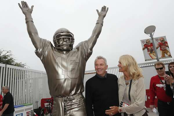 """Former San Francisco 49ers quarterback Joe Montana, center, and his wife Jennifer pose for photos next to a statue of Montana commemorating """"The Catch,"""" which was unveiled along with a statue of wide receiver Dwight Clark, before an NFL football game between the 49ers and the Los Angeles Rams in Santa Clara, Calif., Sunday, Oct. 21, 2018. Clark caught a touchdown pass, known as """"The Catch,"""" from Montana in the NFC Championship game to beat the Dallas Cowboys on Jan. 10, 1982. (AP Photo/Tony Avelar)"""