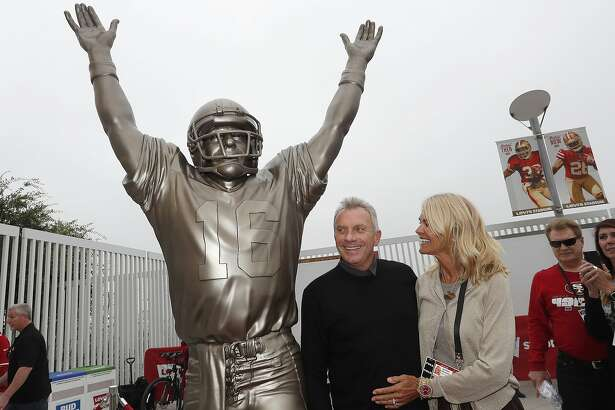 "Former San Francisco 49ers quarterback Joe Montana, center, and his wife Jennifer pose for photos next to a statue of Montana commemorating ""The Catch,"" which was unveiled along with a statue of wide receiver Dwight Clark, before an NFL football game between the 49ers and the Los Angeles Rams in Santa Clara, Calif., Sunday, Oct. 21, 2018. Clark caught a touchdown pass, known as ""The Catch,"" from Montana in the NFC Championship game to beat the Dallas Cowboys on Jan. 10, 1982. (AP Photo/Tony Avelar)"