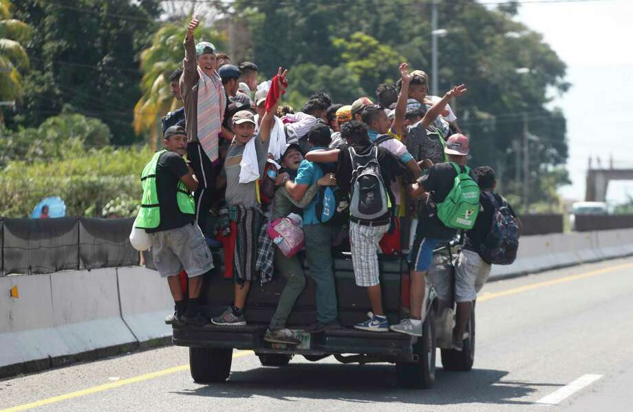 Central American migrants making their way to the U.S. in a large caravan cling on to the truck of a driver who offered them the free ride, as they arrive to Tapachula, Mexico, Sunday, Oct. 21, 2018. Despite Mexican efforts to stop them at the Guatemala-Mexico border, about 5,000 Central American migrants resumed their advance toward the U.S. border Sunday in southern Mexico. (AP Photo/Moises Castillo) Photo: Moises Castillo, Associated Press / Copyright 2018 The Associated Press. All rights reserved.