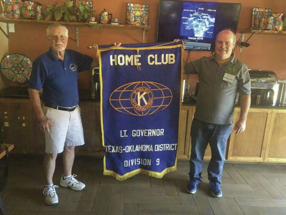 Outgoing LT. Governor Lynn DeGeorge, left, and incoming LT. Governor Daniel Pruett stand with the Kiwanis flag. Pruett was installed this month as the District 9 Lieutenant Governor for the Texas/Oklahoma District in Kiwanis International.