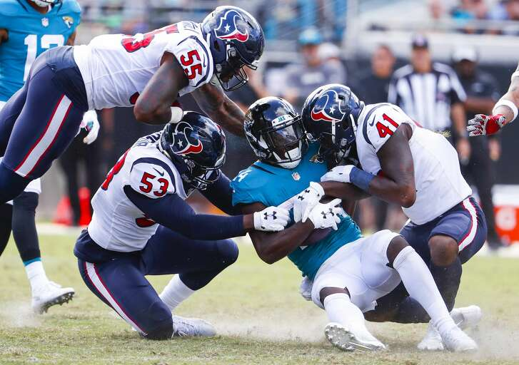 Jacksonville Jaguars running back T.J. Yeldon (24) is brought down by Houston Texans linebackers Benardrick McKinney (55), Duke Ejiofor (53) and Zach Cunningham (41) during the fourth quarter of an NFL football game at TIAA Bank Field on Sunday, Oct. 21, 2018, in Jacksonville.