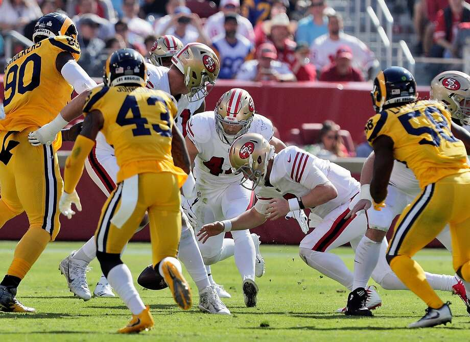 Niners quarterback C.J. Beathard lunges for a fumbled snap in the second quarter. Beathard recovered the ball, but the team committed four turnovers in its loss to the Rams. Photo: Carlos Avila Gonzalez / The Chronicle