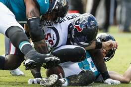 Houston Texans linebacker Whitney Mercilus (59) fights for a fumble after stripping the ball away from Jacksonville Jaguars quarterback Cody Kessler (6) during the fourth quarter of an NFL football game at TIAA Bank Field on Sunday, Oct. 21, 2018, in Jacksonville.