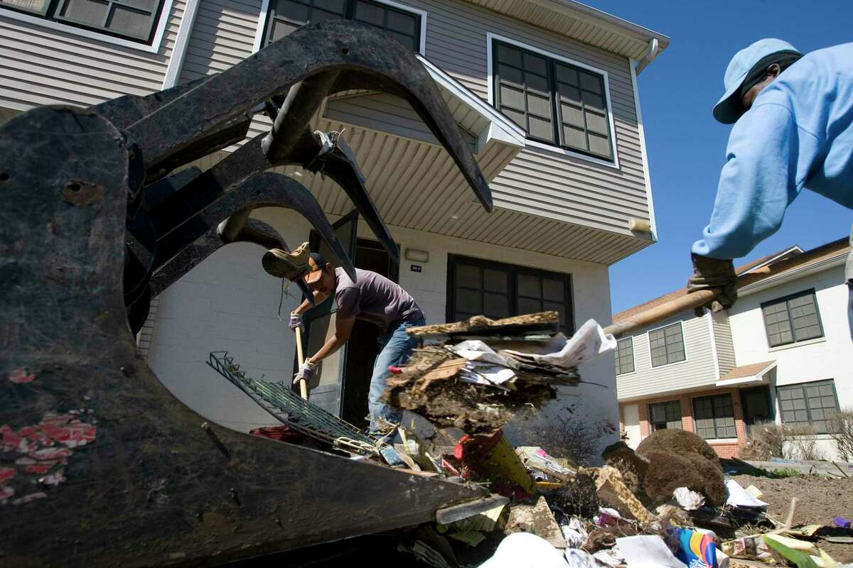 Jose Molina and Jerry Franklin load debris into a front-end loader in the Cedar Terrace Housing Complex in Galveston. Galveston's public housing was destroyed by Hurricane Ike in 2008.