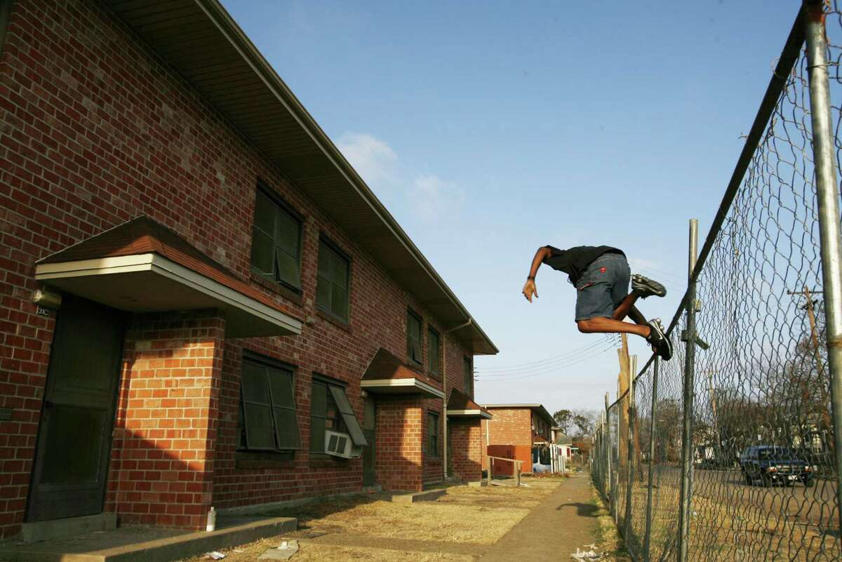 Andre Dickie jumps the fence at the Palm Terrace housing complex to retrieve his furniture in this Oct. 13, 2008, file photo. Palm Terrace was one one of the housing developments later demolished after Hurricane Ike. Ike hit Galveston in September 2008.