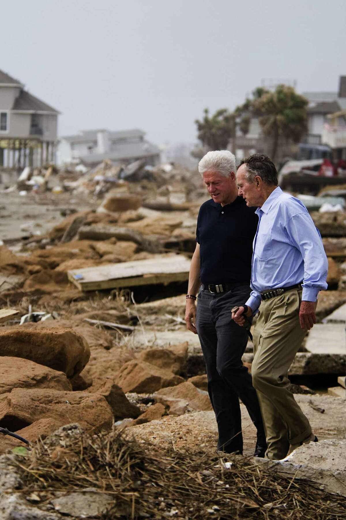 Former U.S. Presidents George H.W. Bush, right, and Bill Clinton walk through debris at Bermuda Beach on Galveston Island as they toured areas affected by Hurricane Ike in this photo from Oct. 14, 2008.