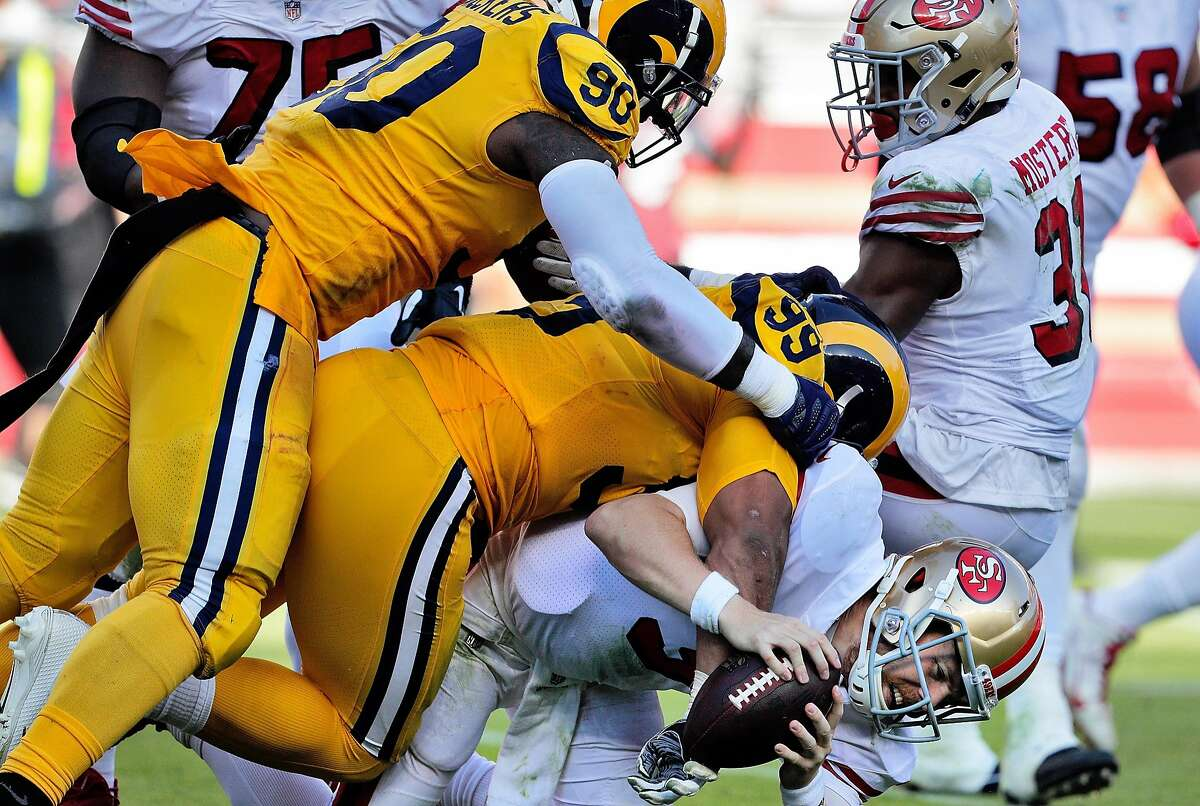 C. J. Beathard (3) is sacked in the fourth quarter by Aaron Donald (99) and Michael Brockers (90) as the San Francisco 49ers played the Los Angeles Rams at Levi's Stadium in Santa Clara, Calif., on Sunday, October 21, 2018.