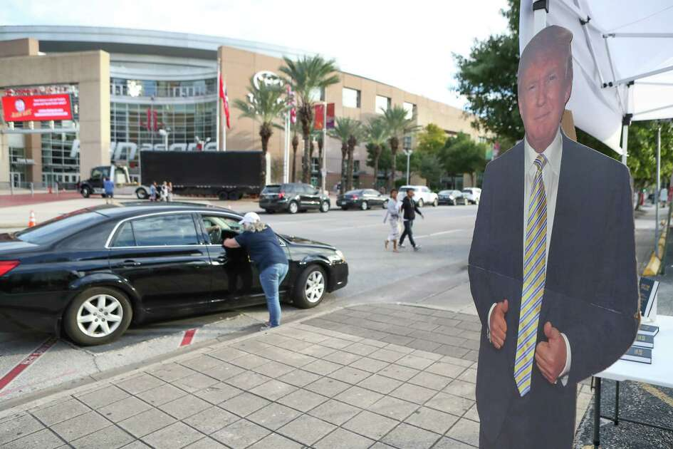 A Trump cut-out stands next to a tent selling the Trump Tweets book before President Donald Trump's rally Monday night at Toyota Center Sunday, Oct. 21, 2018, in Houston.