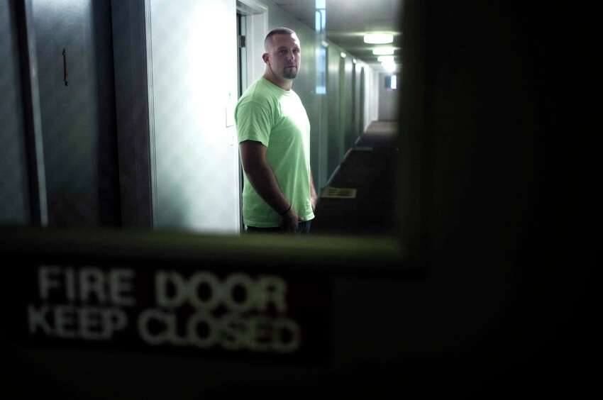 In this Monday, Oct. 1, 2018 photo Michael Robinson, of North Reading, Mass., in recovery from heroin addiction, stands for a photo in a hallway outside his mother's apartment, in North Reading. Robinson recently became a union carpenter and has been working on building projects across the Boston area since. In Massachusetts, with Medicaid expansion already paying for opioid addiction treatment, emergency money from Congress goes largely toward recovery services. (AP Photo/Steven Senne)
