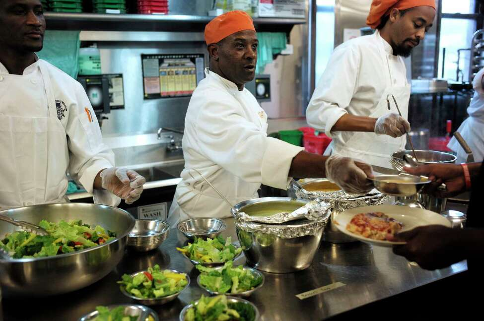 In this Tuesday, Oct. 2, 2018 photo Phillip Oliver, of New Bedford, Mass., center, in recovery from opioid addiction, helps serve a meal in a culinary training program at the New England Center for Arts and Technology, in Boston. In Massachusetts, with Medicaid expansion already paying for opioid addiction treatment, emergency money from Congress goes largely toward recovery services. The state has chosen to use its federal money for those in long term recovery to pay for things like housing, and job training. (AP Photo/Steven Senne)