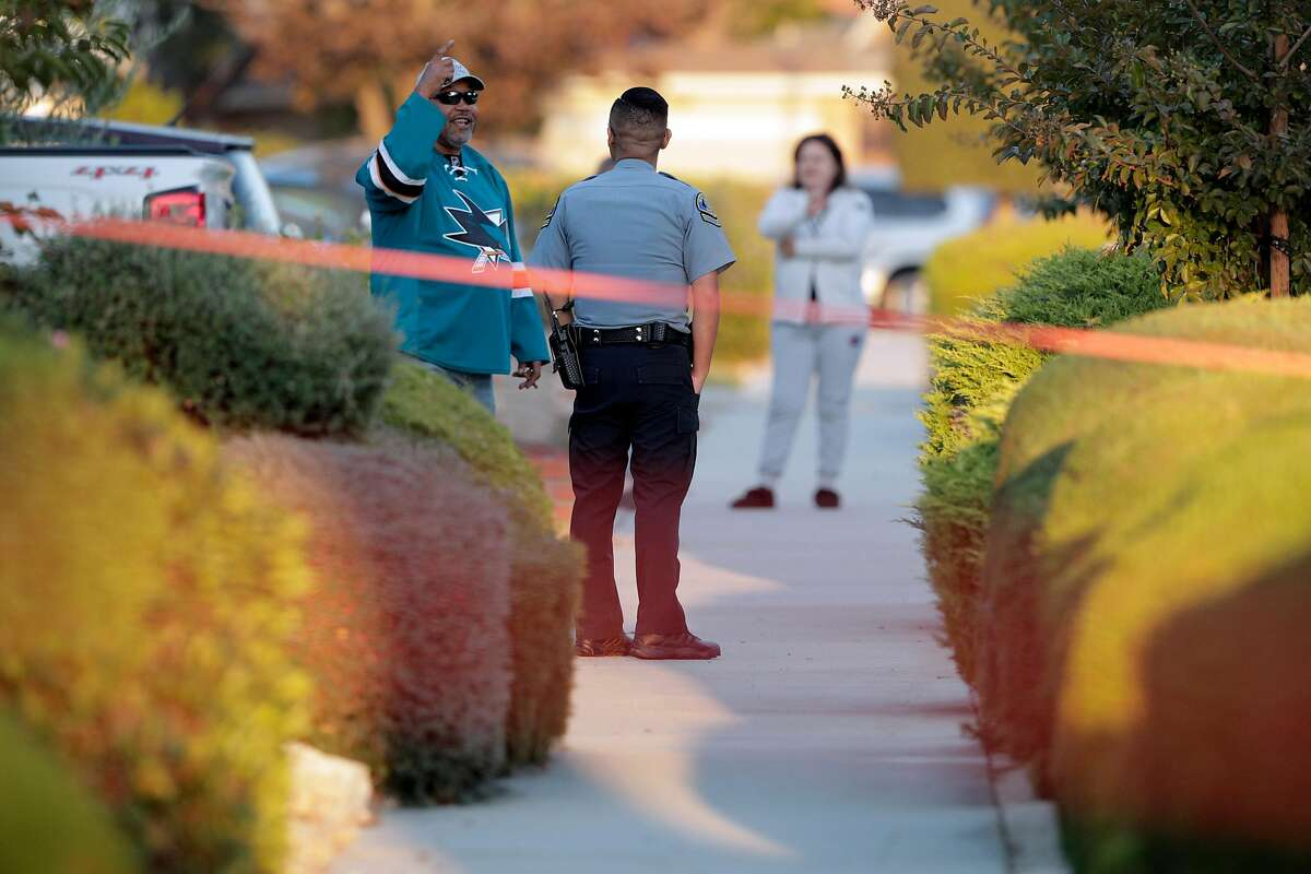 A local resident talks to a San Jose Police officer as others tend to leftover fireworks after two men were injured in an accidental detonation in the garage of a home on Moonflower Court in San Jose, Calif., on Sunday, October 21, 2018.