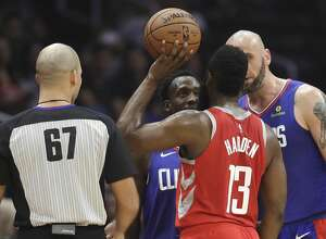 Houston Rockets' James Harden (13) argues after being fouled by Los Angeles Clippers' Patrick Beverley, center, during the first half of an NBA basketball game Sunday, Oct. 21, 2018, in Los Angeles. (AP Photo/Marcio Jose Sanchez)